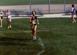 Kathleen (Katie) Webb leads group at a cross-country meet, 1981-1982