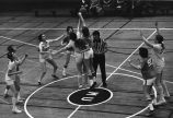 Jane (Fitzmaurice) Burke tips-off basketball while teammates look for ball, 1976