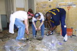 Marquette students rip up floor tiles as a part of Hunger Clean-Up, 2001