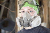 A Marquette student wears a gas mask and goggles as part as she guts a house in New Orleans, 2006