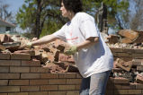 A Marquette student moves bricks in a spring break service trip to New Orleans, 2006