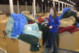 A Marquette student stands amid blankets to be sorted as a part of a Mission Week service project,...