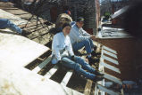 Marquette students take a break from work on a roof, 1995