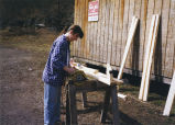 A Marquette volunteer cuts lumber for a Marquette Action Progam project, 1995