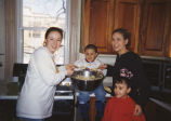 A. Block and Kristin Peterson bake cookies with children at the Detroit Catholic Worker, 1999