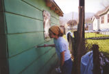Emily Cramer scrapes paint off siding to prepare building for new painting, 2000