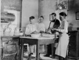 Boys in kitchen with Brother Sturm, S.J., n.d.