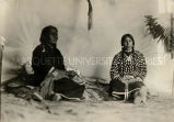 Crow women in tipi wearing trade cloth dresses, n.d.