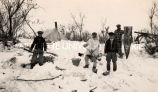 Men at trail camp removing fish from hiding place, 1939?