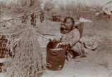 Native woman cleaning herring, 1924? - 1940?