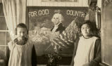 "Girls in front of ""For God and Country"" blackboard sketch, n.d."