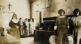 Religious sister and girls in kitchen at St. John's Mission, 1916