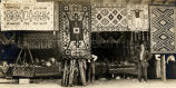 Display of harvest and Navajo rugs at Navajo Fair, 1914