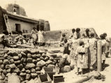 Women daubing mud at Zia Pueblo adobe church, 1920? -1922?