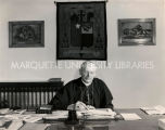 Bishop Espelage of Gallup working at desk, 1940? - 1960?