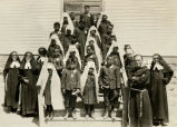 Navajo First Communion class with priests and religious sisters, 1924