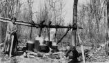 Two women boiling maple sap at sugar camp, 1950?