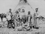 Family in traditional dress (including elk teeth) with blankets and shawls by tipi, 1909