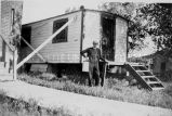 Priest outside trailer, n.d.