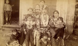 DeRoin family in native dress in front of cabin, 1891?