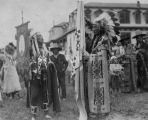 Two men in traditional dress with war bonnets holding church banners, n.d.