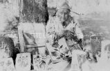 Elder Umatilla woman in native dress with bags and baskets, n.d.