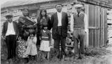 Tom Blind-Man and his family at log cabin, 1932